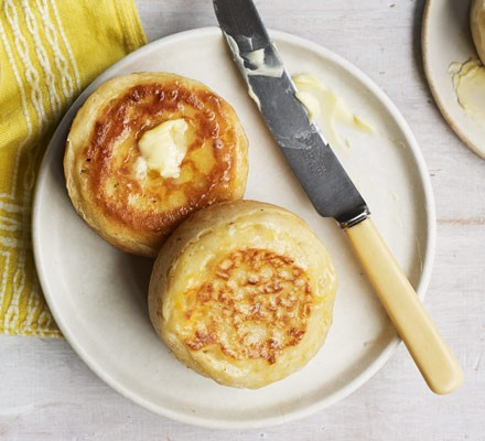 Crumpets on plate with knife and butter