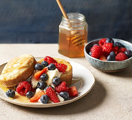 Homemade crumpets with ricotta, berries & thyme honey served on a small plate with honey and berries alongside
