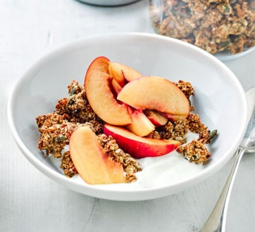 Bowl of granola clusters topped with sliced peaches