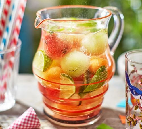 Glass jug of fruity punch filled with melon and cucumber slices