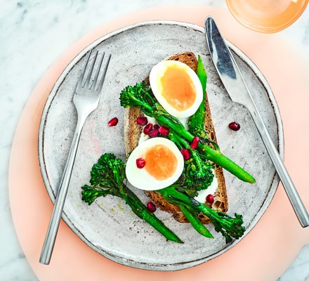 Egg and broccoli on toast on plate with cutlery