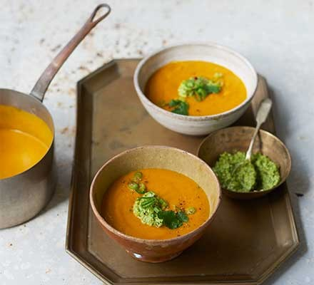 Two bowls of curried carrot soup with cashew & coriander salsa
