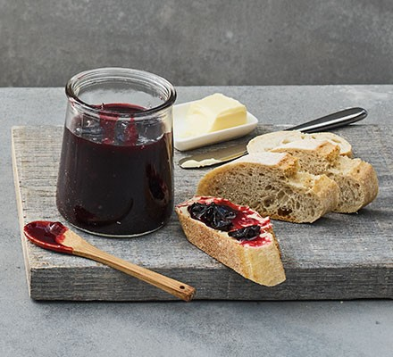 Damson jam in a jar served with crusty bread and butter