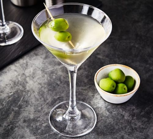A glass of dirty martini with olives on a cocktail stick