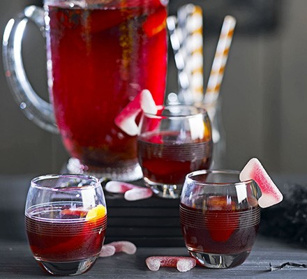 A jug of blood red Halloween punch poured into glasses