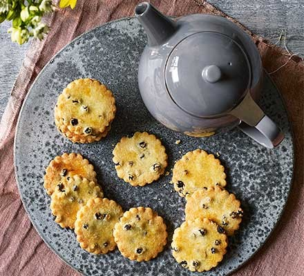 Easter currant biscuits served on a plate with a teapot
