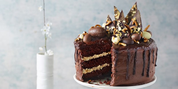 Triple chocolate & peanut butter layer cake served on a cake stand
