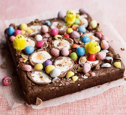 Chocolate brownie traybake topped with mini eggs and colourful chocolates