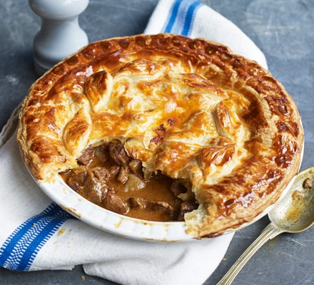 Steak pie in dish with spoon