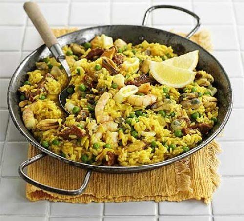 Wide pan of paella rice with seafood and lemon segment