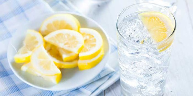 A glass of water with a slice of lemon and ice