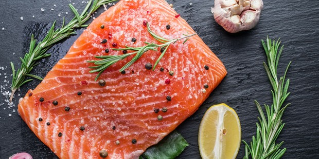 A fillet of salmon on a chopping board with lemon, fresh rosemary and garlic
