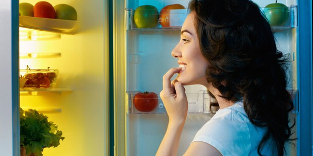 A woman looking in the fridge trying to decide what to eat