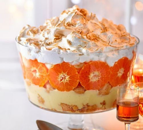 Eggnog trifle with rows of orange segments and meringue topping