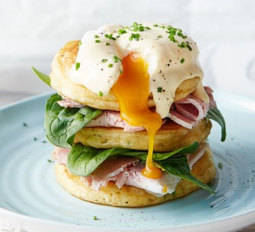 American pancakes with salad and ham layers, topped with runny poached egg