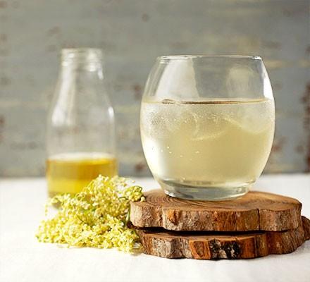 A sprig of elderflower alongside a glass of elderflower gin