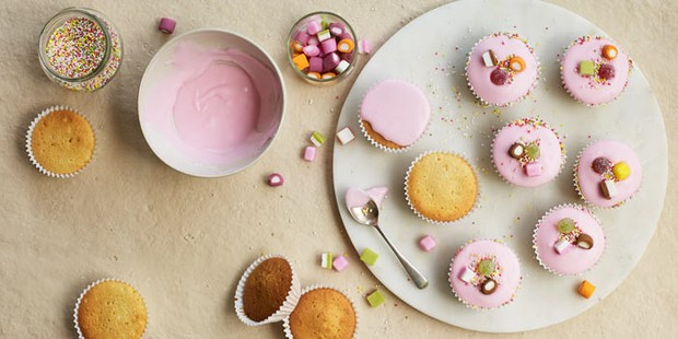 Pink iced fairy cakes with sweets