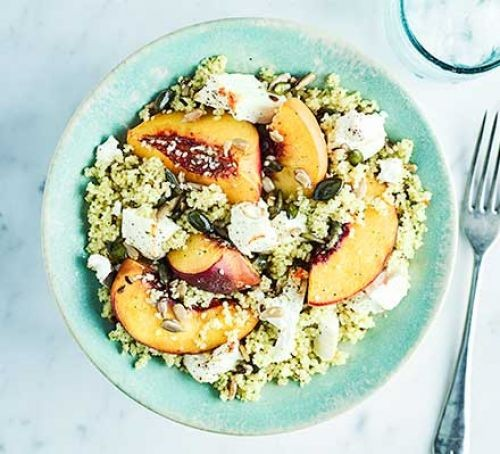 Bowl of couscous topped with sliced peaches and feta