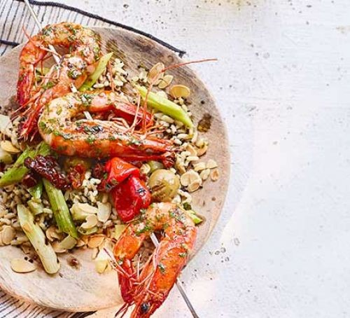 Barbecued prawn and pepper skewers on a plate with rice and salad