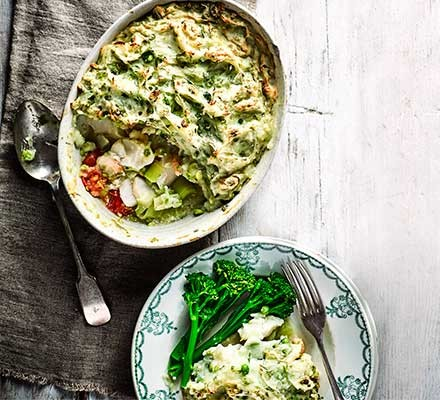 Fish pie with pea & dill mash served in a casserole dish with broccoli