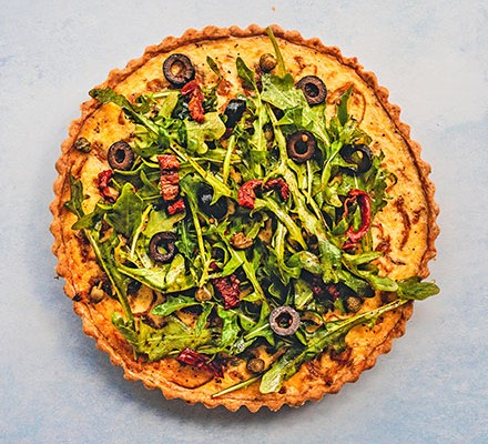 One French onion tart with salad piled on top
