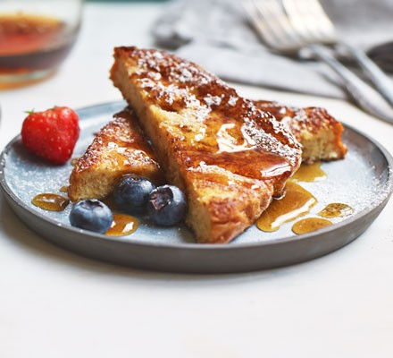 French toast on plate with fresh berries, syrup and icing sugar