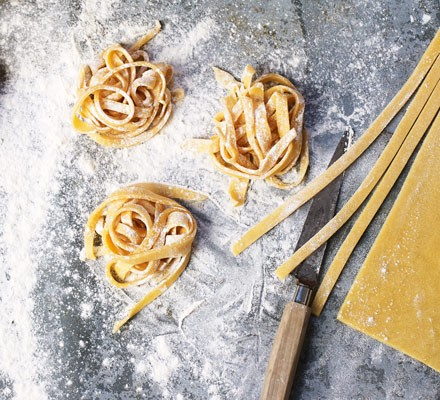 Nests of fresh tagliatelle pasta on a floured surface