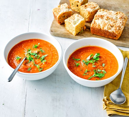 A bowl of tomato soup with cheesy cornbread