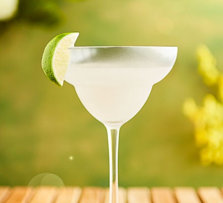 Frozen margarita with lime wedge on glass