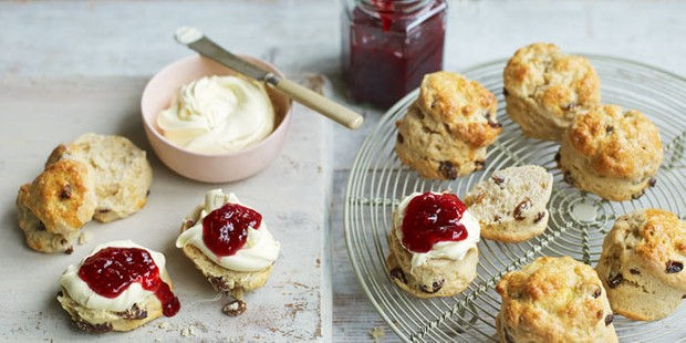 Fruit scones on a wire rack, cut open and served with jam and clotted cream