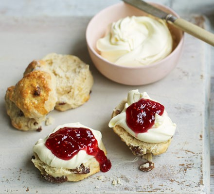 Scones with jam and cream with cream in bowl with knife