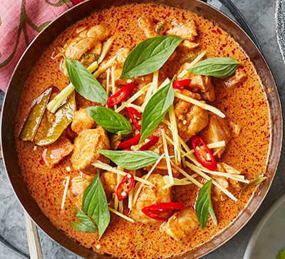Thai red curry with basil and chillies in black bowl