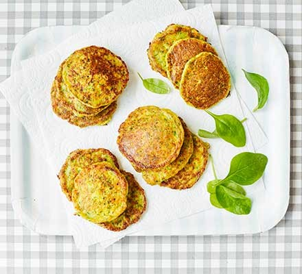 A plate of sweetcorn & spinach fritters on a chequered tablecloth