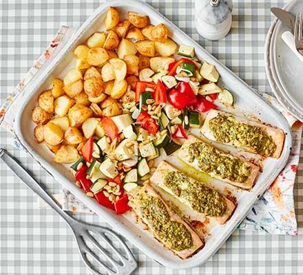 A serving dish with salmon pesto traybake and baby roast potatoes