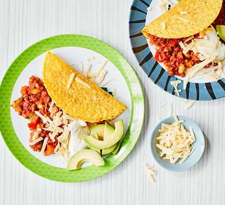 Two plates serving chilli with tacos, avocado and cheese