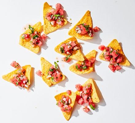 Watermelon salsa on nachos against a white background