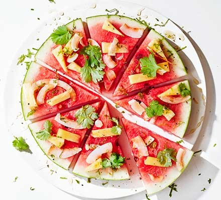 Watermelon and pineapple pizza cut into slices on a white background