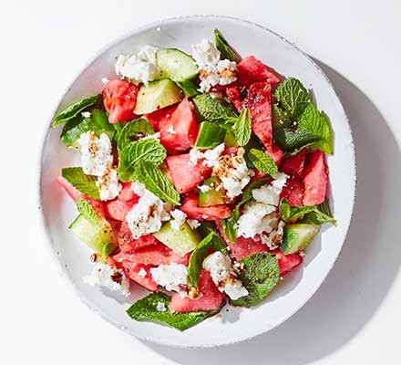 A bowl of watermelon & feta salad garnished with mint leaves