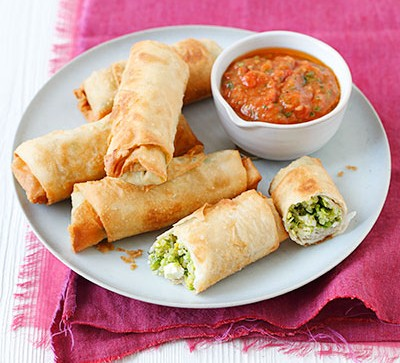 Spring rolls on white plate, dipping sauce and pink placemat