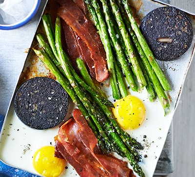 pan of eggs, asparagus and black pudding on blue table