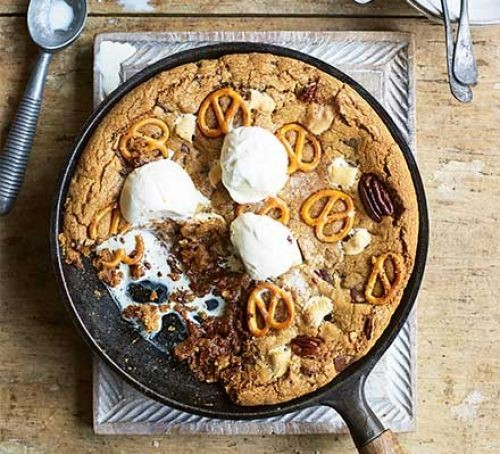 Giant cookie cake with pretzels and ice cream in a pan
