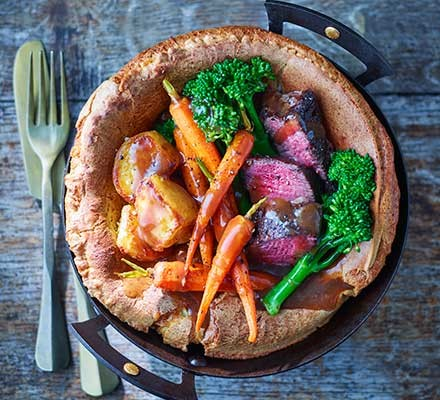Giant Yorkshire pudding Sunday lunch with cutlery served alongside