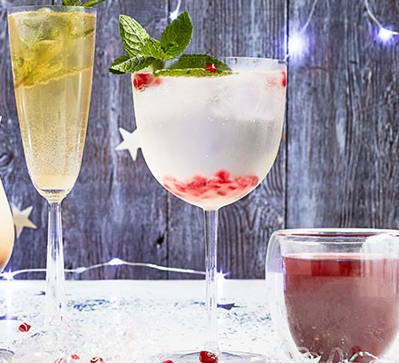 Gin-free G&T served in a large glass and decorated with pomegranate seeds