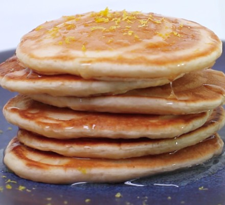 Pancake stack with a sprinkling of lemon zest and a drizzle of syrup