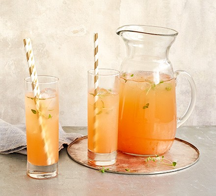 Pink gin iced tea served in a jug and two glasses