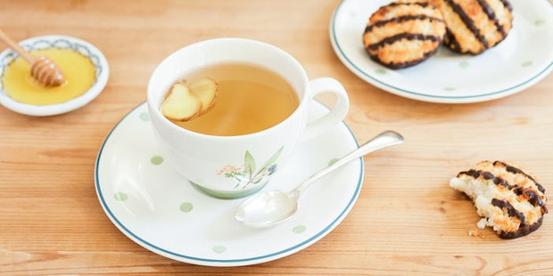 Ginger tea in a white mug along with honey on a plate and macaroons on a plate