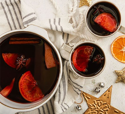 Gluhwein served in a pan with cups alongside