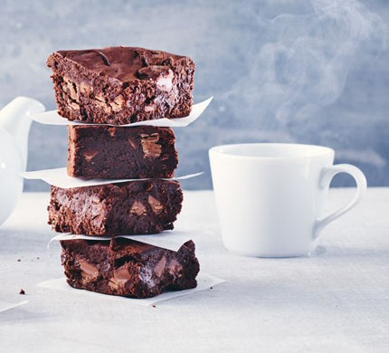 stack of gluten-free chocolate brownies next to a mug