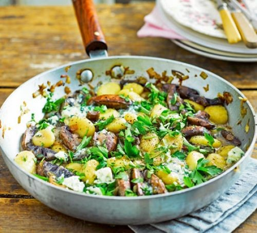 Gnocchi with mushrooms and cheese in pan