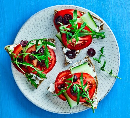 Goat's cheese open sandwiches topped with tomato on plate